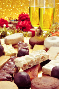 a tray with different turron, mantecados and polvorones, typical christmas sweets in Spain, on a set table with some glasses with champagne and some gifts